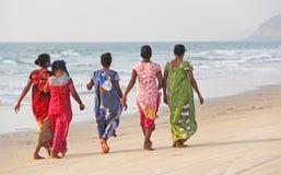 Индия, GOA, 22-ое января 2018 Группа в составе индийские женщины в ярких и красочных сари идет вдоль seashore или пляжа индийско стоковая фотография