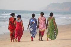 Индия, GOA, 22-ое января 2018 Группа в составе индийские женщины в ярких и красочных сари идет вдоль seashore или пляжа индийско стоковые изображения rf
