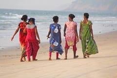 Индия, GOA, 22-ое января 2018 Группа в составе индийские женщины в ярких и красочных сари идет вдоль seashore или пляжа индийско стоковое изображение