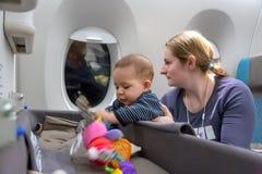 Интерес к особенному bassinet младенца во время полета Первый полет младенческой девушки мать держит младенца в ее оружиях в плос стоковые фотографии rf