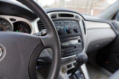 Интерьер автомобиля с рулем, переключением механизма и контролями стоковое фото