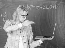 Информация по ее цели Женщина держит ноутбук указывая с жестом оружия на экран Дама воспитателя умная ухищренная с стоковая фотография rf
