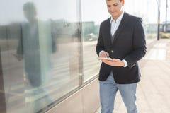 Идя бизнесмен используя снаружи планшета стоковое изображение rf