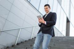 Идя бизнесмен используя снаружи планшета стоковое фото rf