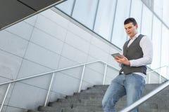 Идя бизнесмен используя снаружи планшета стоковая фотография rf