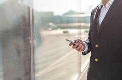 Идя бизнесмен используя снаружи смартфона стоковое фото