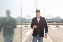Идя бизнесмен используя снаружи смартфона стоковые фотографии rf