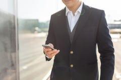 Идя бизнесмен используя снаружи смартфона стоковая фотография rf