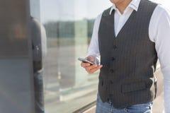 Идя бизнесмен используя снаружи смартфона стоковое изображение rf