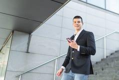 Идя бизнесмен используя снаружи смартфона стоковые фото
