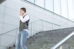 Идя бизнесмен используя снаружи смартфона стоковые изображения rf