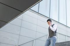 Идя бизнесмен используя снаружи смартфона стоковое фото rf