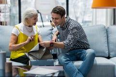 Испуская лучи образец драпирования мебели очаровательной женщины рекомендуя к сыну стоковые изображения rf