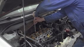 Испытанный механик закручивая с помощью инструменту двигатель от автоматического механика ремонтирует автомобиль для того сток-видео
