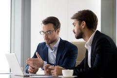 Исполнительные коллеги бизнесменов работая совместно помогать в сыгранности на ноутбуке стоковые изображения