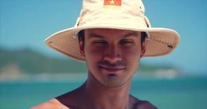 Кавказец близкого поднимающего вверх портрета молодой красивого человека брюнета в шляпе, смотря в камере внимательной, усмехаетс сток-видео