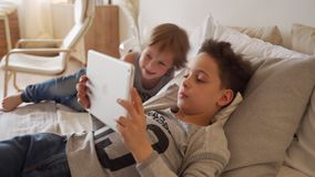 2 кавказских дет, братья мальчика, играя дома в кровати на планшете акции видеоматериалы