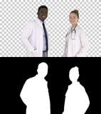 2 кавказское и доктора афро американца усмехаясь стоя смотрящ внутри к камере, каналу альфы стоковое фото rf