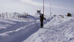 Катание на лыжах и люди лыжника на сноубордах едут вниз с наклона на лыжном курорте в зиме гор акции видеоматериалы