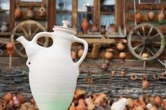 Керамический белый кувшин на предпосылке старого деревянного дома стоковые фотографии rf