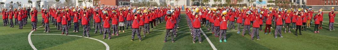 Китайские студенты делают гимнастику баскетбола стоковое изображение rf
