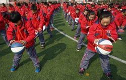 Китайские студенты делают гимнастику баскетбола стоковое изображение