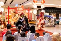 Китайский актер в маске выполняя волшебные фокусы к клиенту который покупки в праздновать торгового центра Bleport стоковые фото