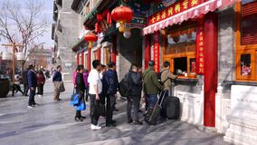Китайский народ стоит в линии на улице Qianmen к традиционно украшенному магазину, Пекин акции видеоматериалы