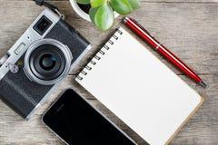 Классическая камера с пустой страницей блокнота и красная ручка на сером деревянном, винтажном столе с телефоном стоковые фотографии rf