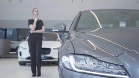 Клиент выбирая автомобиль для покупки Запачканная диаграмма женщины в черном положении носки в мотор-шоу смотря вокруг фара сток-видео