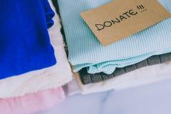 Кучи футболок и одежд будучи сортированными в держат сбрасывание и дарят категории стоковое фото