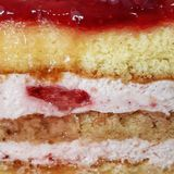 Кусок слоев сливк клубники торта губки стоковая фотография