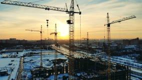 Краны башни на строительной площадке, работая с конструкционными материалами акции видеоматериалы