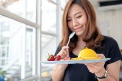 Красивая азиатская женщина держа плиту оранжевого торта со смешанным плодом стоковые изображения