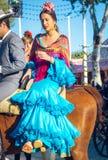 Красивая андалузская молодая женщина с традиционными верховыми лошадьми платья на апреле Севильи справедливо, Севилья Справедлив  стоковые фото