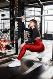 Красивая атлетическая девушка в стильных ярких одеждах спорт делает представления рядом с турником в современном спортзале стоковое фото rf
