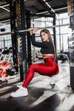Красивая атлетическая девушка в стильных ярких одеждах спорт делает представления рядом с турником в современном спортзале стоковое изображение rf