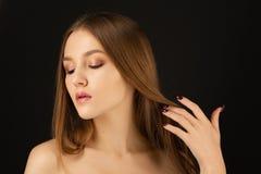 Красивая белокурая модель с розовым лоснистым макияжем на черной предпосылке стоковая фотография rf