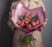 Красивая белокурая девушка держа сочный букет свежих тюльпанов в ее руках стоковые изображения