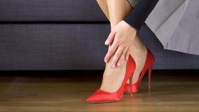 Красивая бизнес-леди принимает красные высокие пятки и массажи тягостные ноги видеоматериал