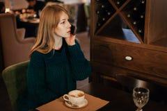 Красивая блондинка молодой женщины выпивает кофе в кафе и говорить по телефону взволнованности стоковые фотографии rf
