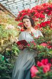 Красивая взрослая девушка в парнике азалии читая книгу и мечтая в красивом ретро платье стоковое фото