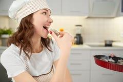 Красивая женщина в печенье дегустации шляпы шеф-повара домодельном стоковые фотографии rf
