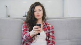 Красивая женщина мирит ТВ и сидит на кресле и держит дистанционное управление в его руке сток-видео