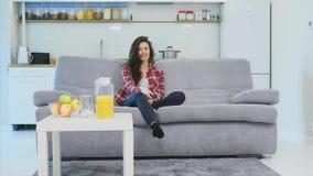 Красивая женщина мирит ТВ и сидит на кресле и держит дистанционное управление в его руке видеоматериал