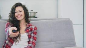 Красивая женщина мирит ТВ и сидит на кресле и держит дистанционное управление в его руке акции видеоматериалы