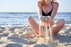 Красивая женщина сидя на песке пляжа печатая в ее руках на предпосылке моря стоковое изображение rf