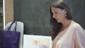Красивая зрелая женщина выбирая стиль причесок в салоне парикмахерских услуг сток-видео