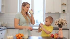 Красивая кавказская мама с длинными белыми волосами лить вне стекло молока для ее милого сына в желтой рубашке самомоднейше акции видеоматериалы