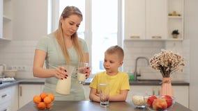 Красивая кавказская мама с длинными белыми волосами лить вне стекло молока для ее милого сына в желтой рубашке самомоднейше сток-видео